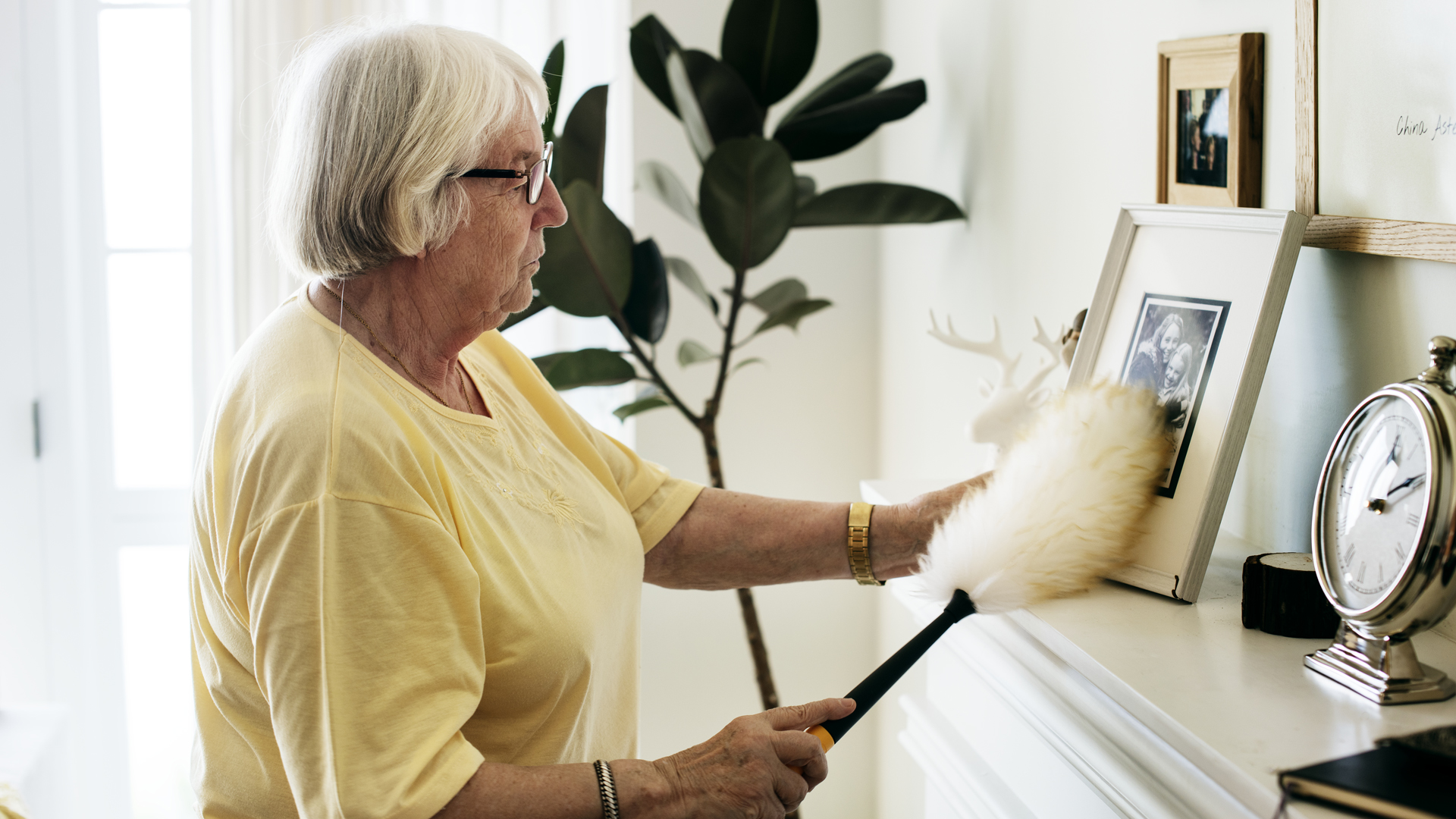 news crop senior-woman-dusting-a-family-photo-PHX7DFU.jpg